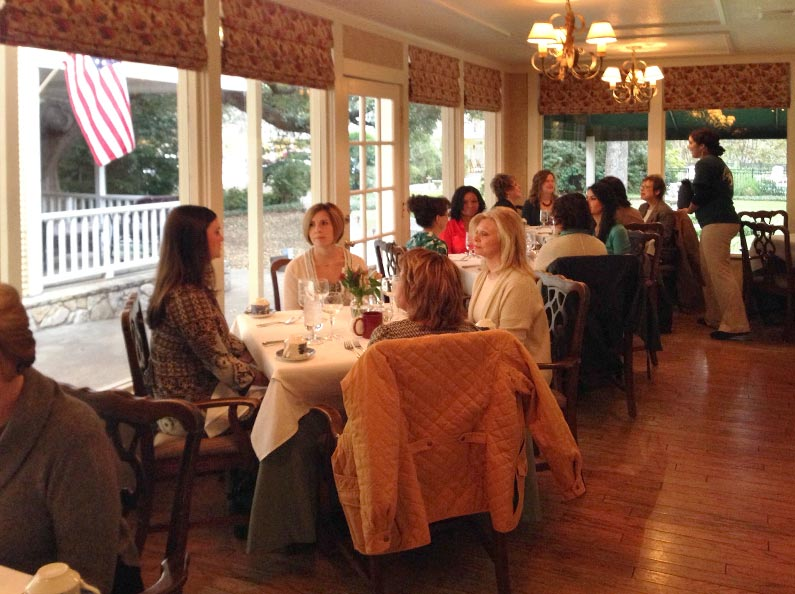 Women receive hands-on dining etiquette instruction at The Art of Confident Living.
