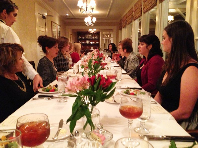 Women practice dining and conversational skills at The Art of Confident Living.
