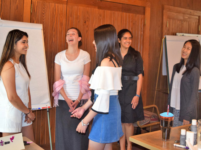 Young women learn and practice handshaking at Deluxe Life Skills Camp.